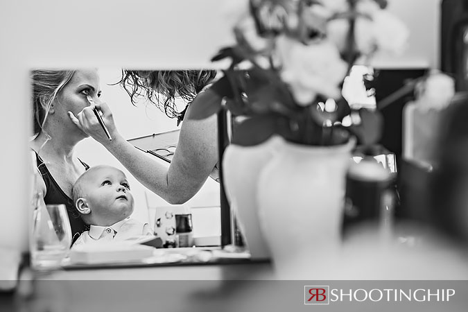 A little boy watches his mum get ready for the wedding
