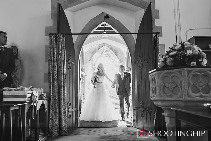 bride enters church with her father