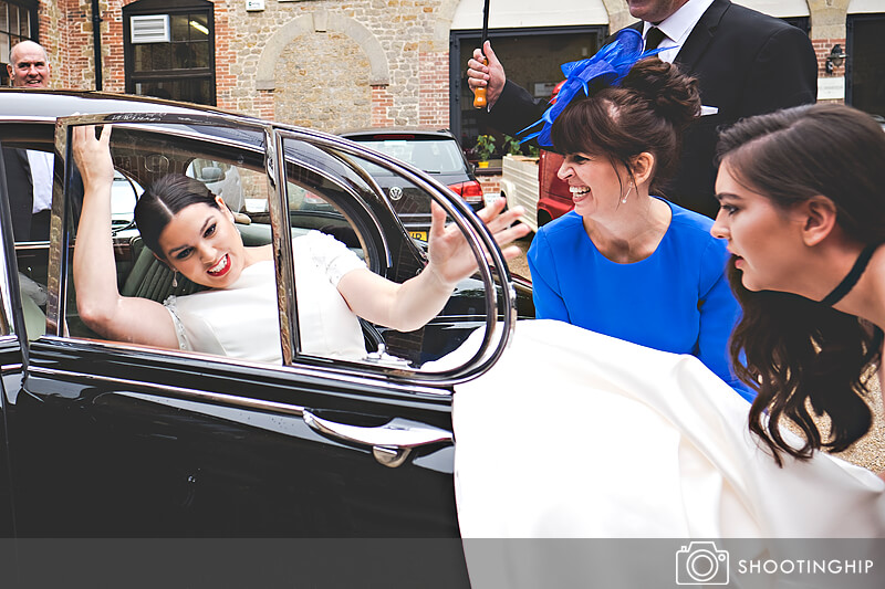 Bride and dress getting into wedding car