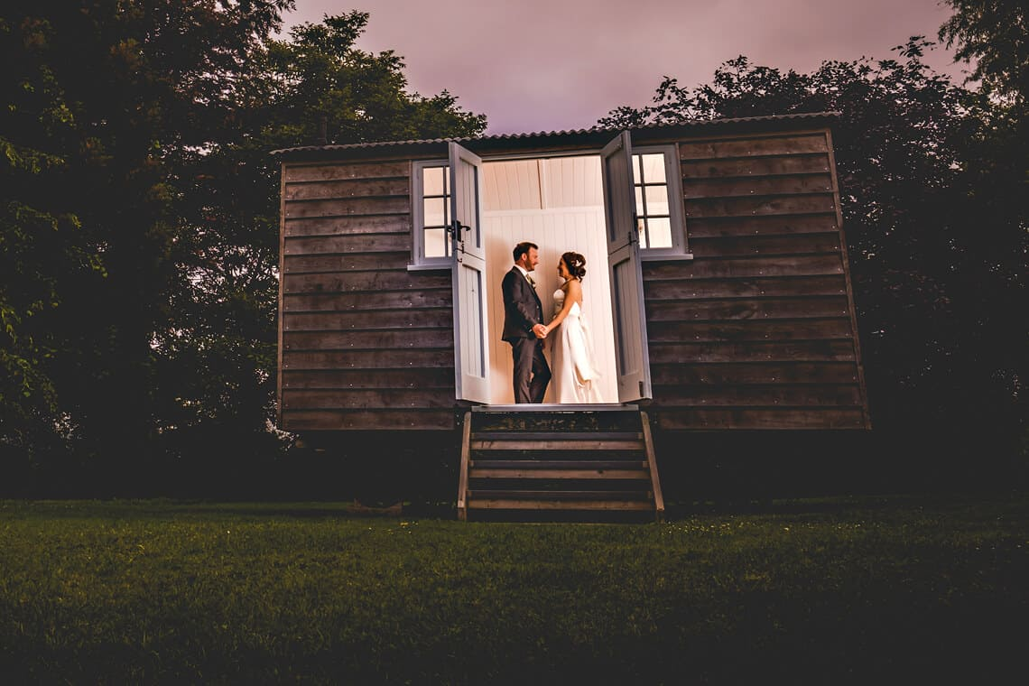 Bride and Groom in Shepherds hut at Tithe Barn