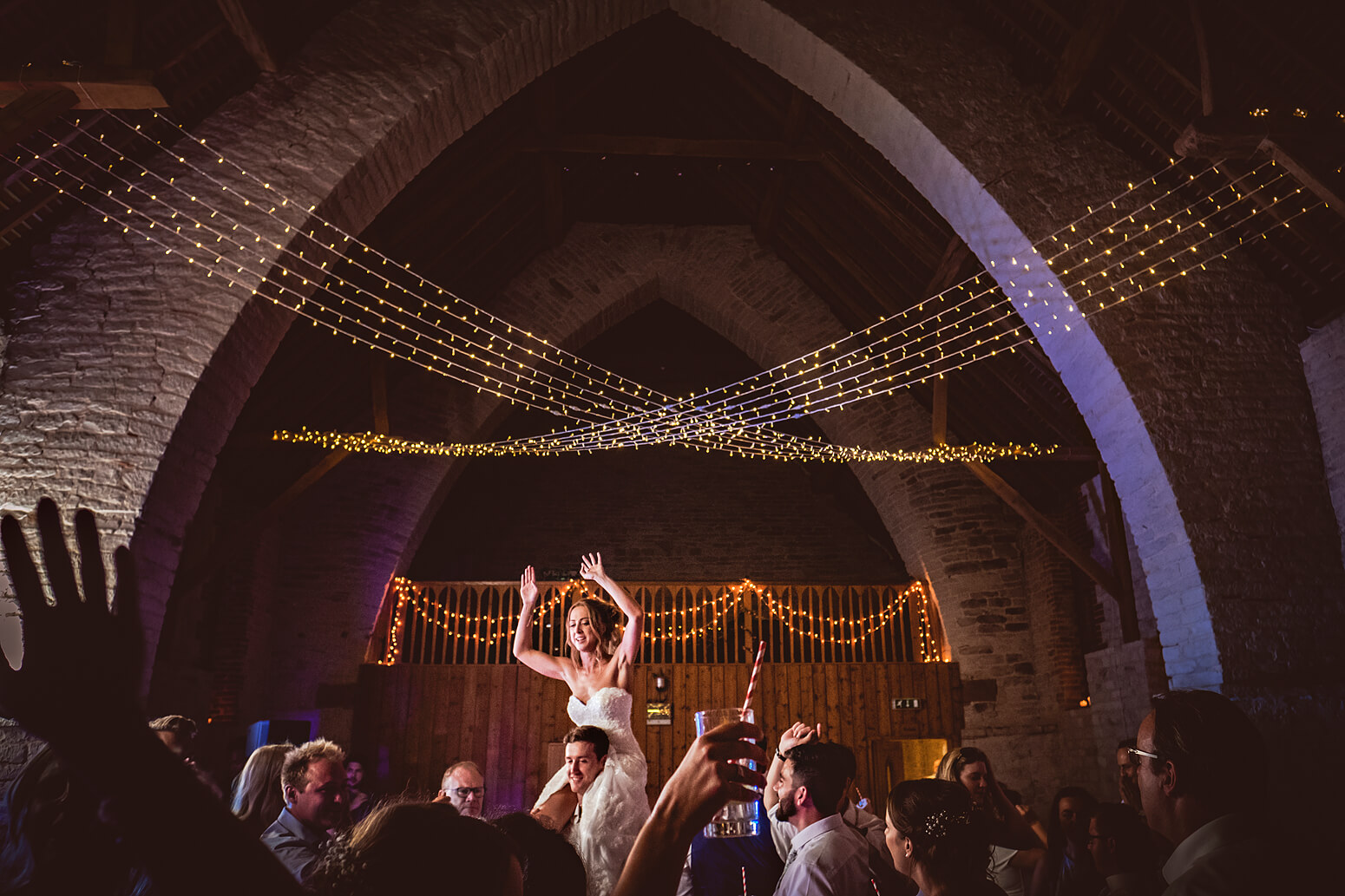 Bride on shoulders at Tithe Barn