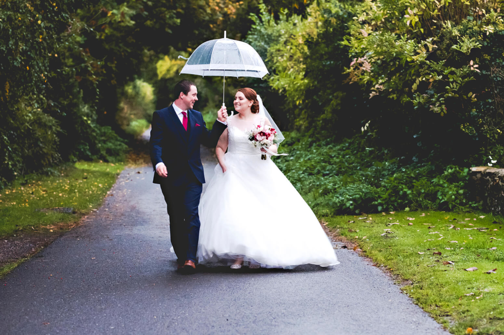 Couple in rain at Tithe Barn