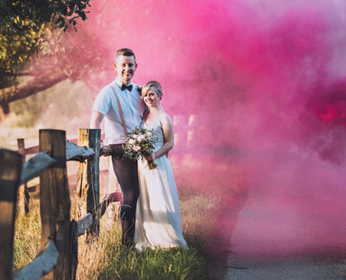 Bride and Groom with smokebombs on a country lane